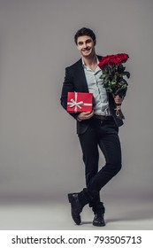 Handsome yound man in suit is posing on grey background with gift box and red roses in hands, looking at camera and smiling.
