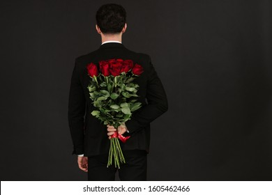 Handsome yound man in suit is standing with red roses behind the back on grey background. Valentines day.