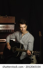 Handsome young acoustic guitar blues player performing his musical skills. Hipster Guitar player strumming. Handsome young male musician playing guitar in recording studio.