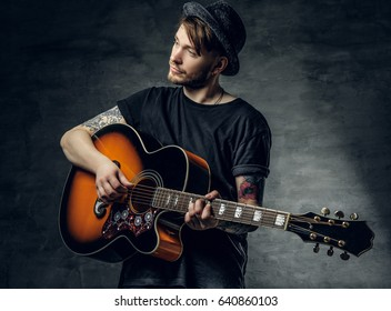 Handsome young acoustic guitar blues player with tattoos on arms performing his musical skills.