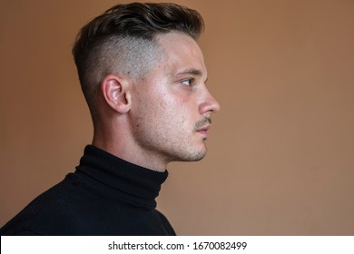 handsome young adult man with undercut hairstyle in profile view. Studio portrait of Man dressed in black turtleneck looking at camera against dark brown background. Shaved whiskey hairstyle