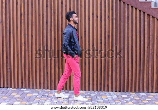 Handsome Young Adult Muslim Man, Businessman Walks Slowly Along Stairs, Looks Around and Smiles, Holds Hands in Pockets of Jackets, Advertises Clothing on Background of Wooden Stairs Near Restaurant
