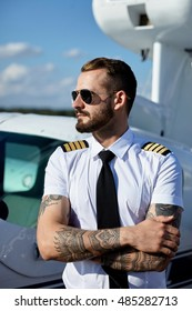 Handsome young adult pilot in sunglasses posing at private motor airplane on runway near hangar.