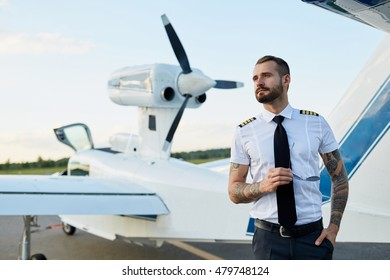 Handsome young adult white pilot with tattoos posing at the private motor aircraft