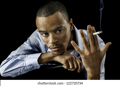 handsome young african american black male looking at a cigarette as if he shouldn't smoke, great concept photo for quitting.