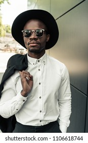 Handsome young african american businessman in sunglasses holding his jacket