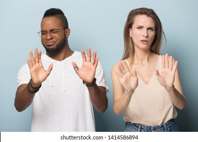 Handsome young african american man in eyeglasses and millennial caucasian woman denying, rejecting proposition, refusing bad deal offer, disagree with possible scam, diverse family couple saying no