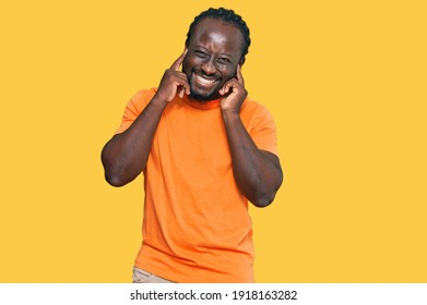 Handsome young african american man wearing casual clothes covering ears with fingers with annoyed expression for the noise of loud music. deaf concept.