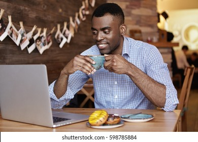 Handsome young African American office worker wearing formal shirt holding mug, enjoying coffee during breakfast, sitting in front of open laptop pc, reading article on online men's magazine