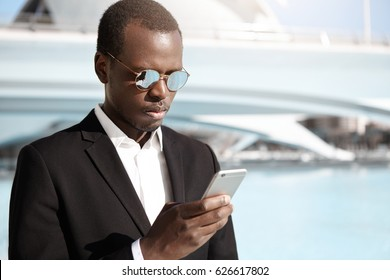 Handsome young African American office worker in elegant black suit and eyewear standing in urban surroundings, looking concentrated while trying to call cab using online app on his mobile phone
