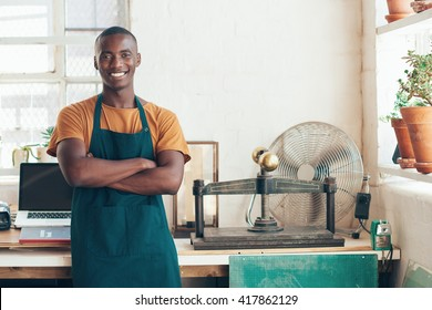 Handsome young African artisan smiling confidently in beautifull studio