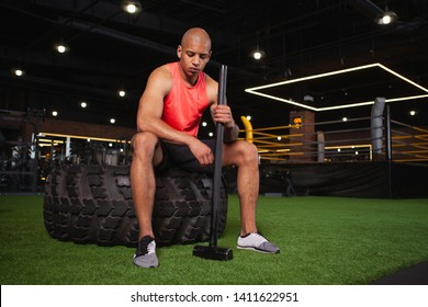 Handsome young African fitness man relaxing at the gym after exercising with heavy sledgehammer and huge tire, copy space. Attractive bodybuilder resting after doing sledgehammer exercise