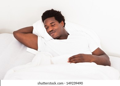 Handsome Young African Male Sleeping In Bed At Home