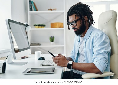 Handsome young African man in eyewear using smart phone while working in the office