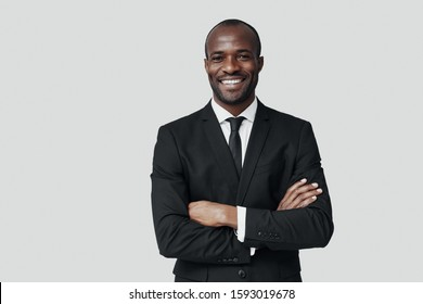 Handsome young African man in formalwear looking at camera and smiling while standing against grey background