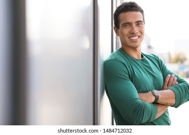 Handsome young African-American man near wall on city street. Space for text