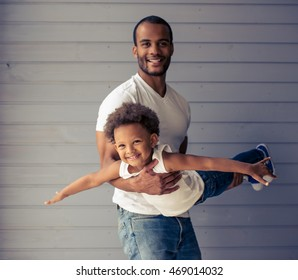 Handsome young Afro American father and his cute child are looking at camera and smiling while playing together. Kid is imitating an airplane
