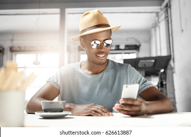 Handsome young Afro American male tourist wearing hat and trendy shades smiling happily while reading sms on smart phone, messaging his girlfriend online using free wi-fi, having coffee at cafe