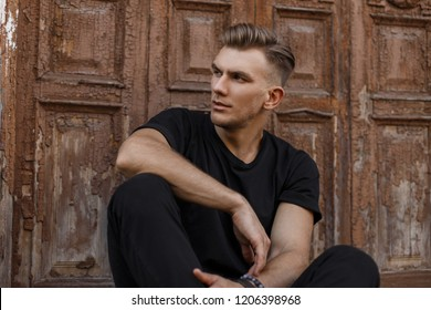 Handsome young american model man with hairstyle in black trendy t-shirt sitting near a vintage wooden door