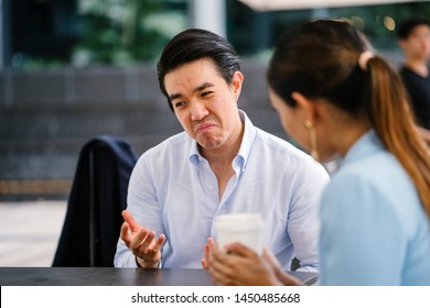 A handsome and young Asian business man in a crisp white shirt is talking to a woman in a suit. He is making a reluctant, grudging and unimpressed expression on his face as he thinks something over.