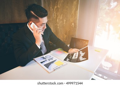 Handsome Young asian businessman by workplace and speaking on the phone.