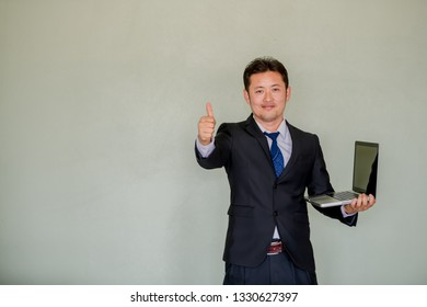 A handsome young Asian businessman smiling using Notebook.