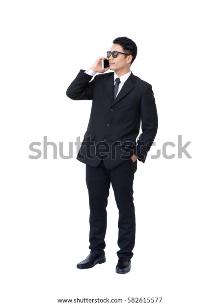 Handsome young asian businessman in a suit while using smart phone and standing on white background.