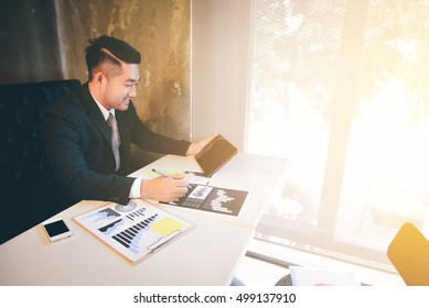 Handsome Young asian businessman working be smile and happy at work.