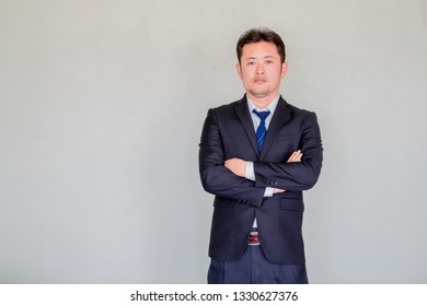 A handsome young Asian businessmanin office suit posing