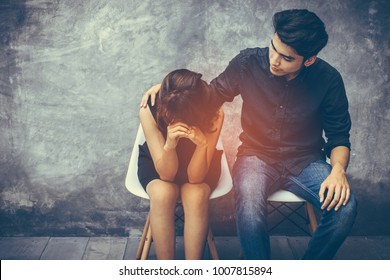 Handsome young Asian hand holding the shoulder to show encouraging women dressed in black who are grieving about something. He had two people sitting on a white chair the meeting room a cement wall.