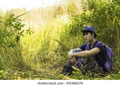 Handsome young Asian hipster relaxing with hat on meadow - Nature and Travel concept with young man sitting in the park. Young Asian Backpacker man in spring grass.