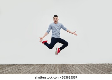 Handsome young Asian man jumping in the street