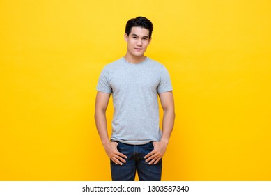 Handsome young Asian man in plain light gray t-shirt studio shot isolated on colorful yellow background