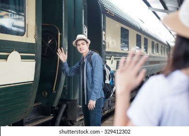 Handsome Young Asian man say goodbye to girlfriend at train station before journey. Young Asian man sent hand sign to goodbye.