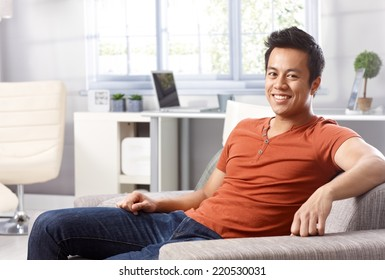 Handsome young Asian man sitting at home on sofa, smiling happy, looking at camera.