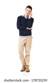 Handsome young Asian man take a call, full length portrait isolated on white background.