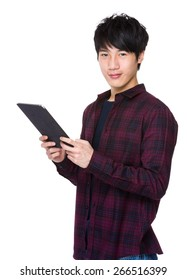 Handsome young asian man using pad