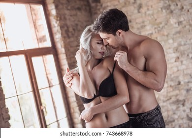 Handsome young athletic man with bare torso and sexy young woman in black lingerie are kissing and hugging before having a sex