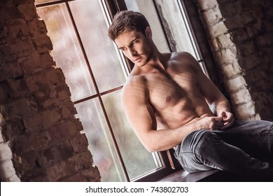 Handsome young athletic man with bare torso is looking out the window and thinking while sitting on window-sill