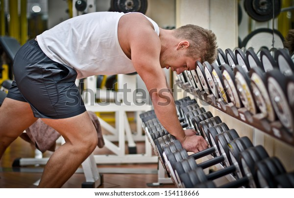Handsome young athletic man resting on dumbbells rack after workout in gym