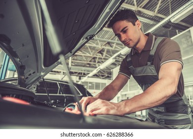 Handsome young auto mechanic in uniform is repairing car in auto service
