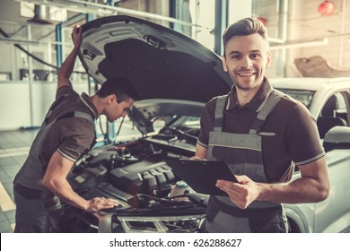 Handsome young auto mechanics in uniform are examining car while working in auto service
