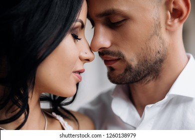 Handsome young bald headed man hugs with passion young brunette in pink evening dress