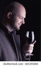 Handsome young bald man smelling red wine before tasting and drinking it. Man wearing spring coat and holding a glass of red wine in his hand. Low key portrait. Toned