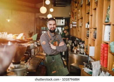 Handsome young barista with beard looking at camera and smiling while standing at the bar counter at cafe in a gray plaid shirt and green brown apron
