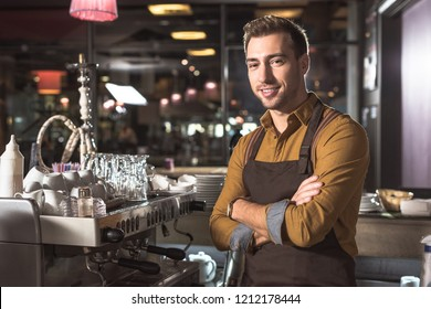 handsome young barista with crossed arms standing near coffee machine and looking at camera
