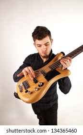 Handsome young bass player holding the bass high