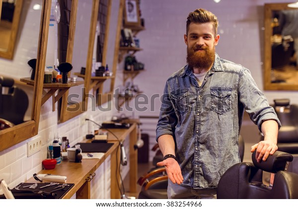 Handsome young bearded barber pointing on a chair, looking at camera and smiling while standing in the barber shop
