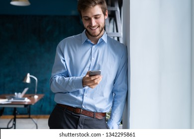 handsome young bearded business man in office using mobile phone indoors