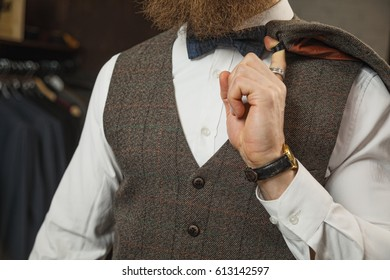 Handsome young bearded businessman in classic suit. A young stylish man in a black cloth jacket. It is in the showroom, trying on clothes, posing. Advertising photo